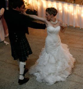 wedding couple dancing on the dance floor. The lady wearing a beautiful gown while the man is in a Kilt they are dancing their 1st dance as an official married couple