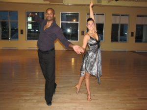 African American male and white french quebecer female in New York Dance Position. He is wearing male black latin dance shoes, black pants and a purple top while she is wearing skin tone female latin dance shoes, a silver and black dress both looking stunning cha cha lessons toronto access ballroom studio