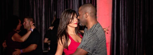 black man and white woman, brunette dancing Bachata and he is wearing a grey t-shirt, she is wearing a red top with lipstick to match, beautiful, gorgeous doing Salsa Lessons Toronto