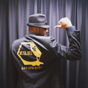 MC Gil Bee in uniform showing the back of the suit representing Emcee Toronto phone# 647-376-5191 showing on the back of the suit jacket and the colour is black
