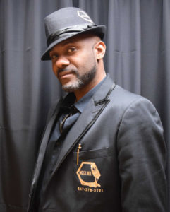 MC Gil Bee in uniform showing the front of the suit representing Emcee Toronto phone# 647-376-5191 showing on the front of the suit jacket and the colour is black