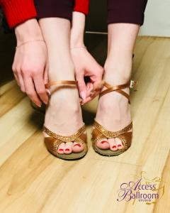 a girl woman putting on latin dance shoes before her private dance lessons toronto at Access Ballroom Studio ABS-Toronto