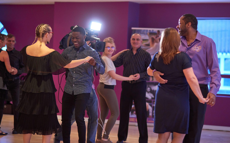 Access Ballroom teaching Brandon Gonez from CP24 to dance